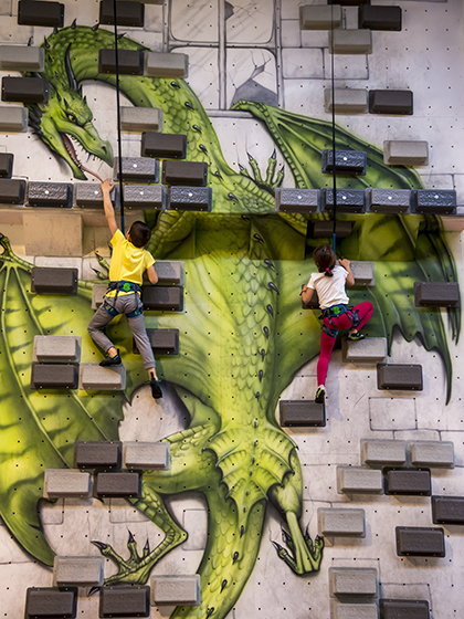 Niños pequeños escalando en el rocódromo.