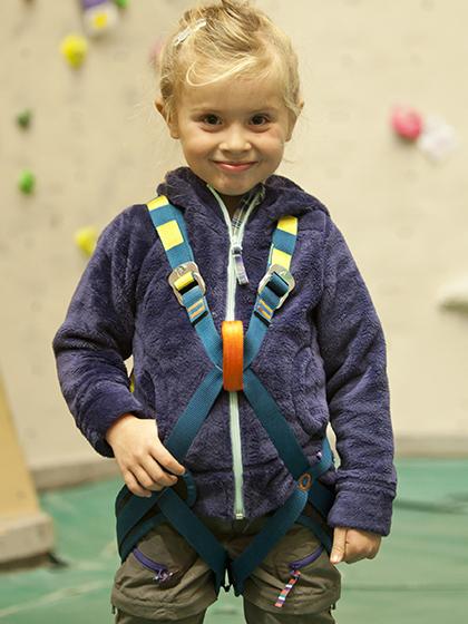 Niño escalador con arnés completo.